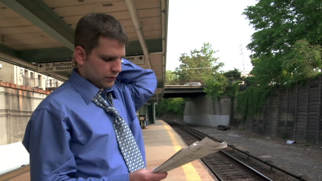 Young male professional reading newspaper while waiting on platform for commuter train / New York