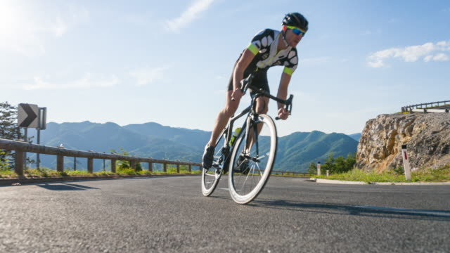 young male road cyclist pushing himself to reach the top of the mountain pass - cycling event stock videos & royalty-free footage