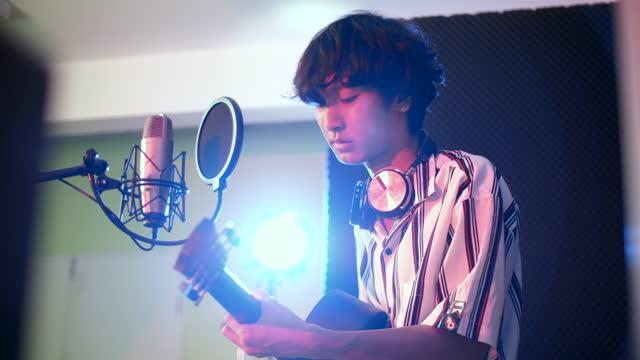 vídeos y material grabado en eventos de stock de joven rockero masculino grabando música con guitarra en estudio, concepto de estudio de grabación - 20 24 años