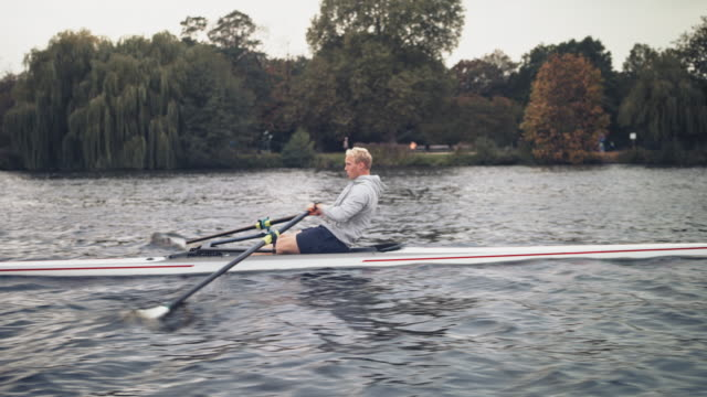young male rowing boat in river - sculling stock videos & royalty-free footage