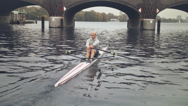 young male rowing rowboat in river - arch bridge stock videos & royalty-free footage