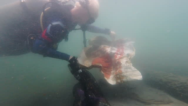 stockvideo's en b-roll-footage met young male scuba diver rescues marine life from plastic pollution - red sea
