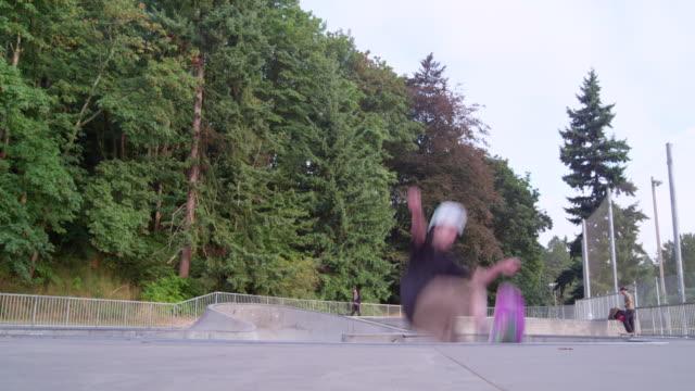 vídeos y material grabado en eventos de stock de ms slo mo young male skateboarder performing a trick in mid air in neighborhood skate park - un solo adolescente