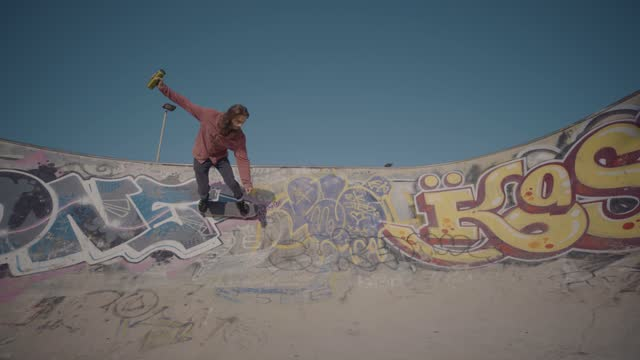 young male skater with long hair skates around a bowl in a city skate park decorated with graffiti, on september 09 2020, in bristol, united kingdom. - hobbies stock videos & royalty-free footage