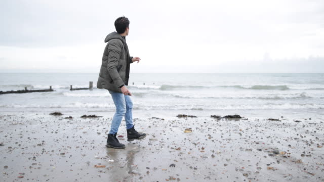 young male skimming stones on a beach in winter - ein mann allein stock-videos und b-roll-filmmaterial