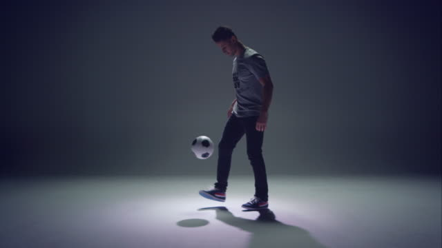 young male soccer freestyler is doing kick-ups. - juggler stock videos and b-roll footage