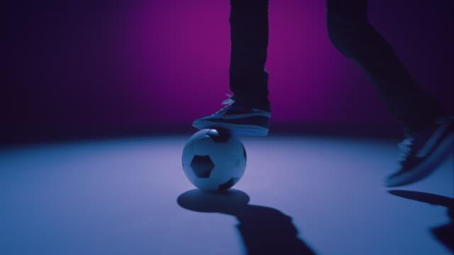 Joven hombre freestyler de fútbol con una pelota está driblar