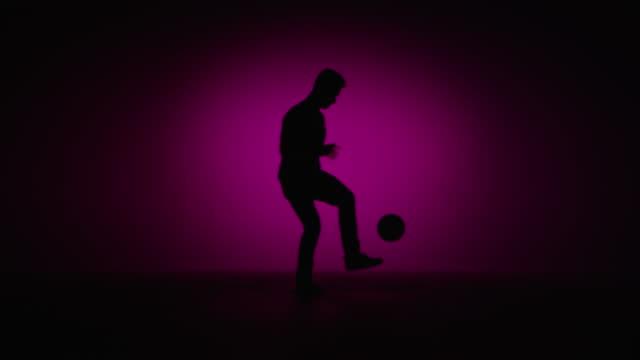 vídeos de stock e filmes b-roll de jovem macho freestyler de futebol é rematar a bola - retroiluminado
