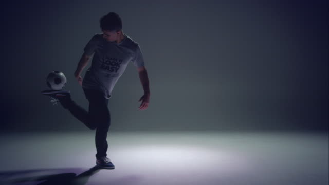 young male soccer freestyler is showing his kick-ups skills.