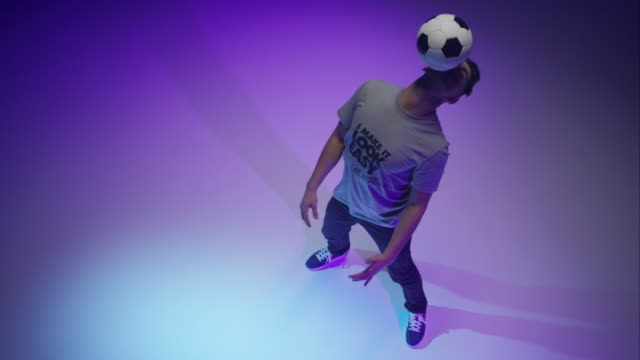 young male soccer freestyler juggling a ball around his head - human head stock videos & royalty-free footage
