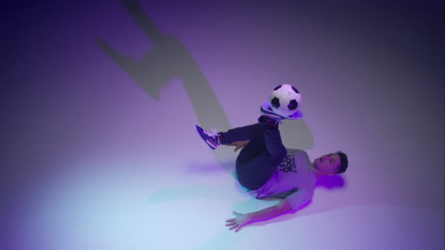 young male soccer freestyler juggling a ball on his brines