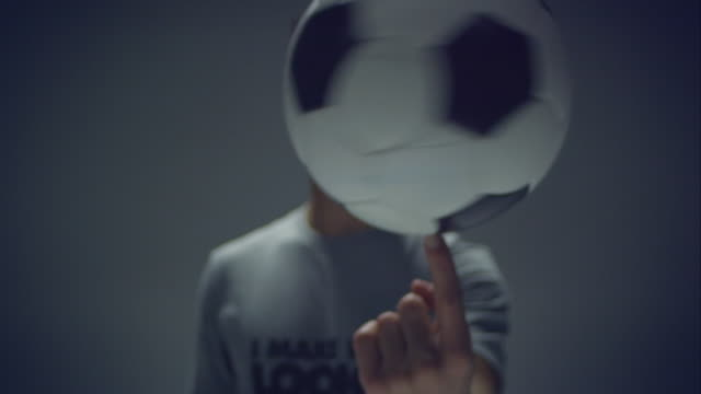 young male soccer freestyler spins a ball on his fingers