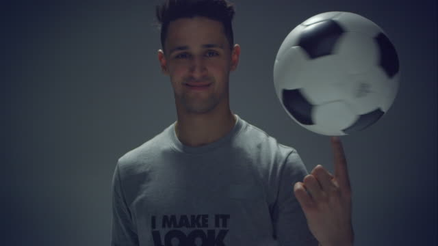 young male soccer freestyler spins a ball on his fingers - stunt stock videos and b-roll footage