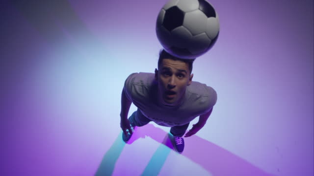 young male soccer freestyler throwing a ball with his head - football player stock videos & royalty-free footage