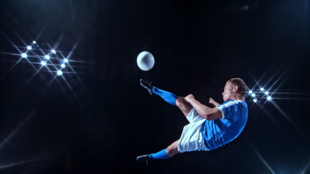 SLO MO LD Young male soccer player in blue jersey kicking the ball with a scissor kick on a black background