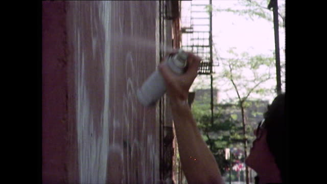 young male spray paints a wall in new york;1976 - graffito stock-videos und b-roll-filmmaterial
