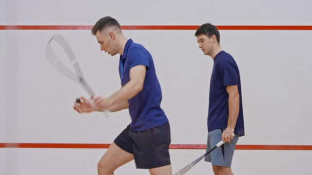 young male squash coach teaching a male student - squash sport stock videos & royalty-free footage