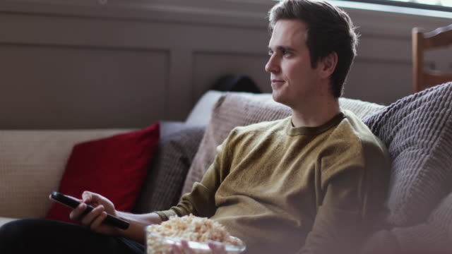 Young male streaming movie at home eating popcorn