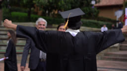 Young male student hugging his parents while holding up his degree and parents looking very proud