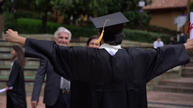 young male student hugging his parents while holding up his degree and parents looking very proud - graduation stock videos & royalty-free footage