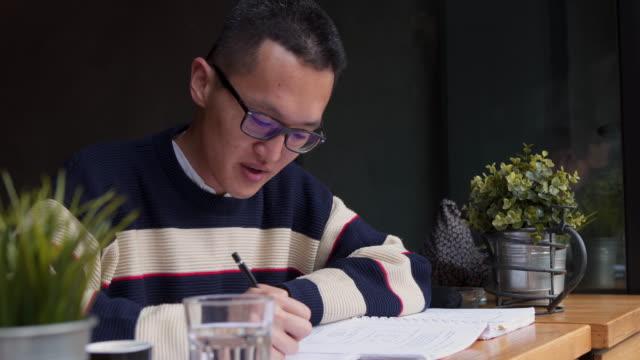 junge männliche schüler notizen für seine prüfungen - east asian ethnicity stock-videos und b-roll-filmmaterial