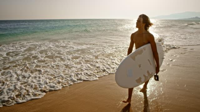 vídeos de stock e filmes b-roll de slo mo young male surfer walking down a sandy beach carrying his surf board - só um homem jovem