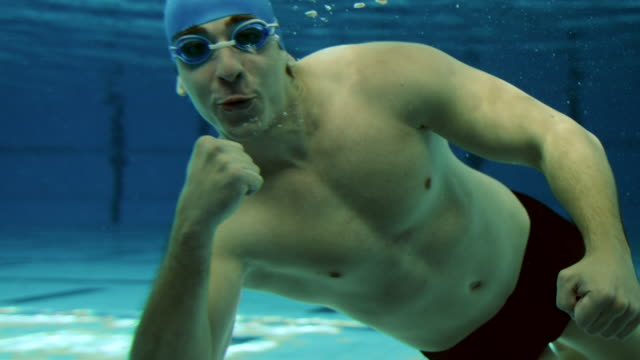 Young male swimmer smiling and showing thumbs up