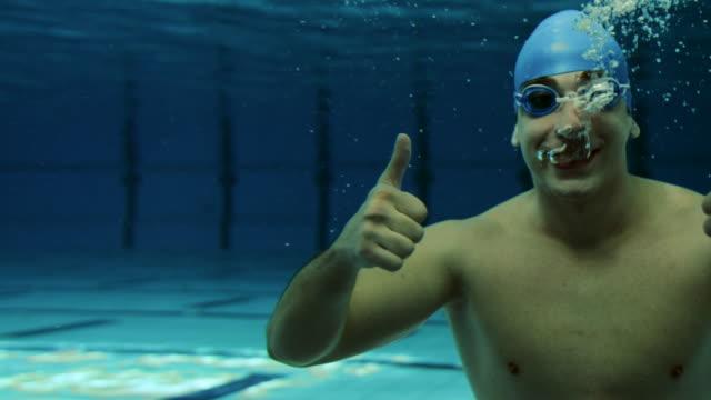 vídeos de stock, filmes e b-roll de jovem macho nadador sorrindo e mostrando polegares para cima - prendendo a respiração