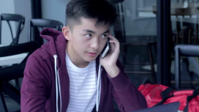 young male talking on his cellphone at a cafe - philippines stock videos & royalty-free footage