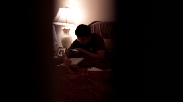 a young male teenager is writing in bed at night - one teenage boy only stock videos & royalty-free footage