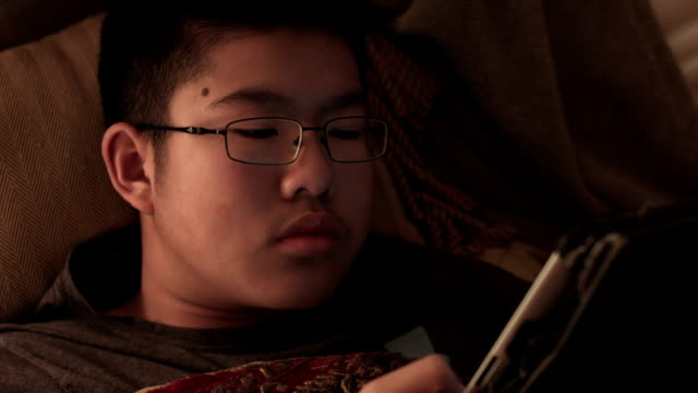 a young male teenager using digital tablet in bed at night - one teenage boy only stock videos & royalty-free footage