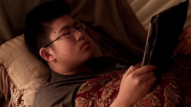 stockvideo's en b-roll-footage met a young male teenager using digital tablet in bed at night - alleen één tienerjongen