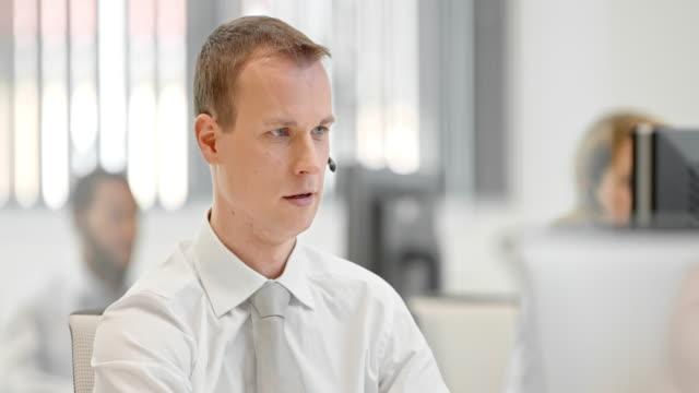 tu giovane maschio operatore telefonico parlando di un cliente - offrire un servizio video stock e b–roll