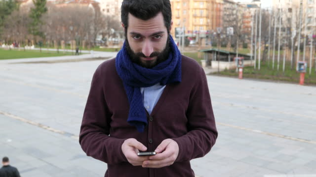 young male texting and looking at camera - staring stock videos & royalty-free footage