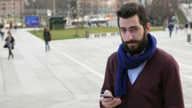 Young male texting and looking at camera