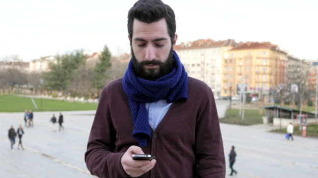 Giovane maschio ricevere tweet e messaggi di testo, guarda alla macchina fotografica