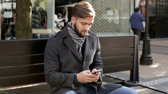 Young male texting on smart phone