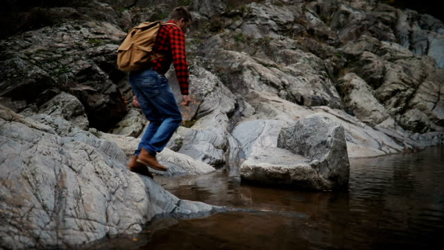 A young male tourist crosses a mountain river in the forest