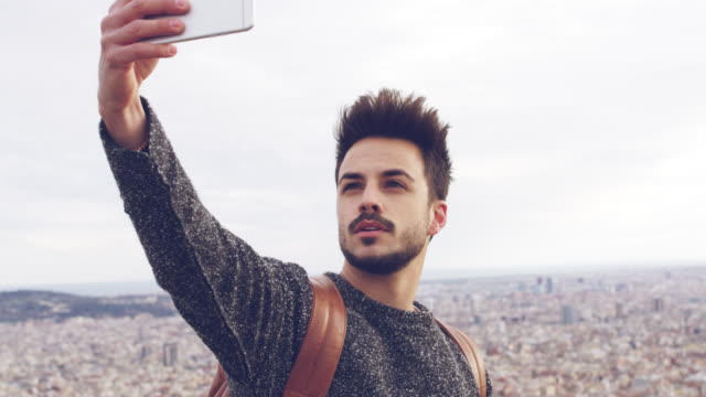 young male tourist taking selfie against cityscape - handsome people stock videos & royalty-free footage