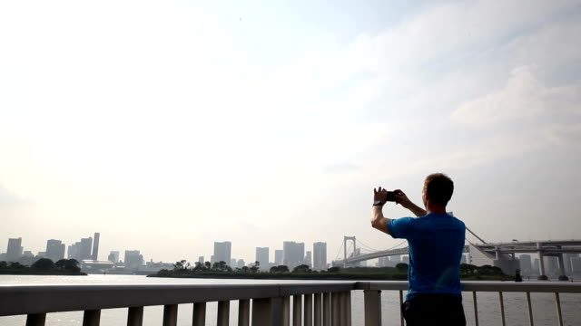 Young male tourist uses phone to take a picture of Tokyo City