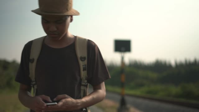 a young male tourist using mobile phone walking on road - country road stock videos & royalty-free footage