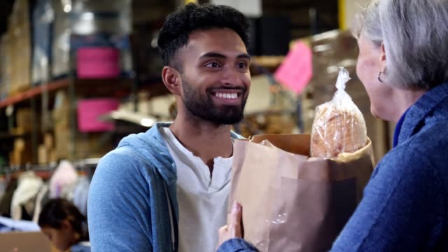 a young male volunteer hands groceries to senior woman - regole dell'etichetta video stock e b–roll