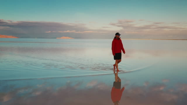young male walking on the flooded bonneville salt flats at sunset shot from a low angle panning shot, utah, united states of america - bonneville salt flats stock videos & royalty-free footage