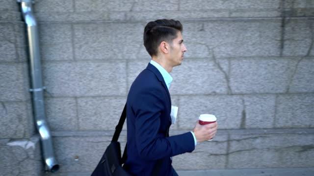 Junge Männer gehen auf der Straße und hält seinen Kaffee und Zeitung