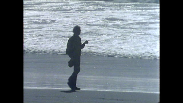 young male walks along the beach in san francisco - water's edge stock videos & royalty-free footage