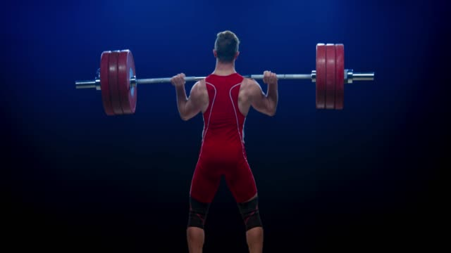 young male weightlifter performing the clean and jerk lift to lift the barbell at a competition - sports equipment stock videos & royalty-free footage