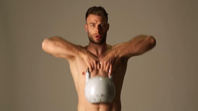 vídeos y material grabado en eventos de stock de joven macho haciendo ejercicio con kettlebell en estudio - vestido parcialmente