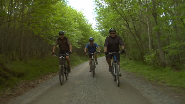 2 young males cycling in the forest towards camera and awa - see other clips from this shoot 1036 stock videos and b-roll footage