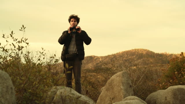 young man, 25-years-old traveling hipster, observing the nature with the binocular from the elevated rocky point near by devil dance floor in the yosemite national park - canocchiale video stock e b–roll