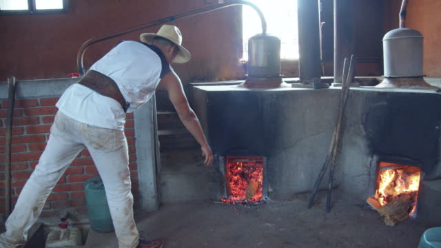 young man adding a log to the mezcal distillation still firewood. homemade distillation process at a family business. santiago de matatlan, oaxaca, mexico - firewood stock videos & royalty-free footage